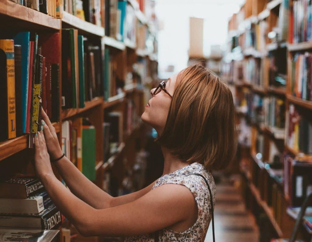 Frau sucht Bücher in Bibliothek