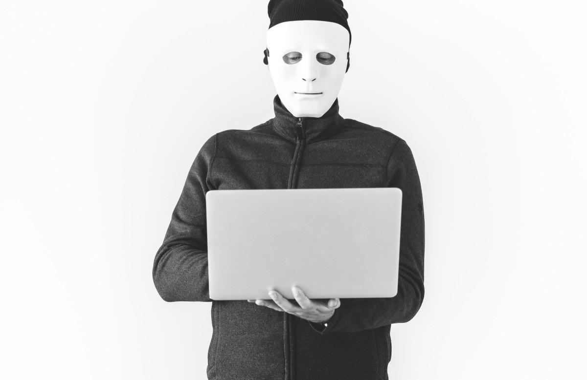 Hacker mit Maske und Laptop