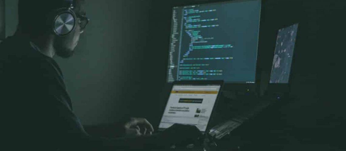 Ein IT-System Administrator arbeitet nachts am Rechner